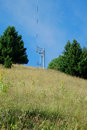 Ski lift track in the summer looking up at a with wire towers on a grassy mountain side during Stock Photography