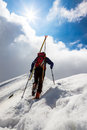 Ski mountaineer walking up along a steep snowy ridge with the s skis in backpack in background dramatic sky shiny Royalty Free Stock Photos
