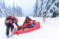 Ski patrol with rescue sled injured woman helping women snow forest Stock Image