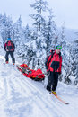 Ski patrol transporting injured skier snow forest members carry downhill rescue stretcher Stock Photos