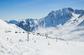 Ski slope in the winter pyrenees a sunlit downhill with skiers and an aerial lift are photographed against snow covered mountains Stock Photo