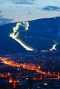 Ski slopes above city night view on lights and snow on with fis course on pohorje mountain with traffic and lights of maribor Stock Photo