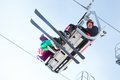 Ski vacation snowboarders and skiers scope out the run as they ride the chairlift to the top Royalty Free Stock Photography