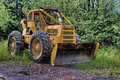 Skidder rigged with a snow plow parked away in the summer Stock Images