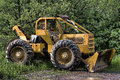 Skidder rigged with a snow plow parked away in the summer Royalty Free Stock Photos