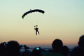 Skidiver approaching the silhouette of an skydiver against sunset sky Stock Images