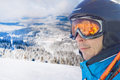 Skier man in the blue skiing jacket, helmet and glasses against snow forest panorama Royalty Free Stock Photo