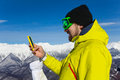 Skier man texting with cell phone over mountain Royalty Free Stock Photo