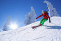 Skier skiing downhill in high mountains against sunset colorful Royalty Free Stock Image