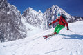 Skier skiing downhill in high mountains colorful Royalty Free Stock Photography