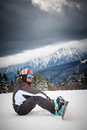Skier in snowy mountains male with ski fastenings sat under dark clouds on mountain Stock Photos