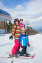 Skiing winter family two happy smiling kids in ski goggles and a helmet with his mother in the mountains Stock Photography