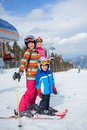 Skiing winter family two happy smiling kids in ski goggles and a helmet with his mother in the mountains Royalty Free Stock Photos