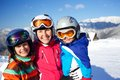 Skiing winter family two happy smiling kids in ski goggles and a helmet with his mother in the mountains Royalty Free Stock Images