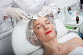 Skillful female beautician is undergoing laser treatment professional making cavitation peeling for mature woman she cleaning Stock Photography