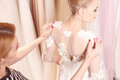 Skillful female tailor is fitting bridal clothing