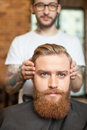Skillful male barber is serving his client Royalty Free Stock Photo