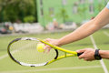 Skillful male tennis player ready for competition close up of young athlete arms beating a ball by racket man is standing in Stock Image