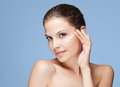 Skin care beauty portrait of a beautiful young brunette using lotion Stock Image