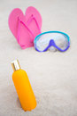 Skin care concept close up of suntan lotion bottle diving mas mask and flip flops on summer sandy beach Royalty Free Stock Photos