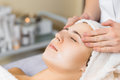Skin care medical beautician makes massage face after applying mask Stock Image
