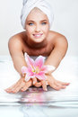 Skincare beautiful young woman in white towel on her head with flower in hands in water reflection Stock Photos
