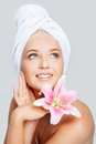 Skincare close up face of young beautiful woman in white towel with pink lily on gray background Stock Image
