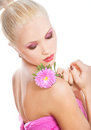 Skincare portrait of beautiful blond woman with pink flower on naked shoulder on white background Stock Image