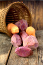 Skinned sweet potato purple and orange with leaves and basked background on wooden table Royalty Free Stock Image