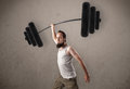 Skinny guy lifting incredible weights funny Royalty Free Stock Photography