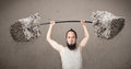 Skinny guy lifting large rock stone weights funny Royalty Free Stock Photo