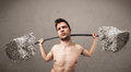 Skinny guy lifting large rock stone weights funny Stock Images