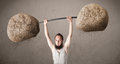 Skinny guy lifting large rock stone weights funny Stock Photo