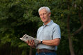 Skinny happy old man reading book in the park outdoor Stock Photography