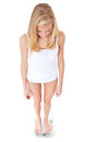 Skinny woman on body scale standing all white background Stock Image