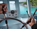 Skipper hands on a steering wheel of a boat motoring in tropical sea Stock Photo