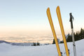 Skis and mountain panorama iii a set of poles rest upright in the snow at the precipice of a steep slope Royalty Free Stock Photos