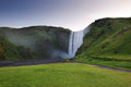 Skogafoss waterfall behing green cliffs, South Iceland Stock Photo