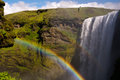 The skogarfoss troll a rainbow thrown by facing waterfall in iceland Stock Photography