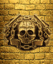 Skull, golden guns and chain on a background of golden brick wal