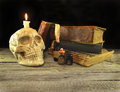 Skull with old books halloween still life of scary human and burning candle Royalty Free Stock Images