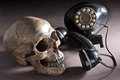 Skull with old telephone Royalty Free Stock Photo