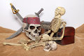 Skull and swords pirate of the Caribbean with Old wooden chest on the brown fabric. Royalty Free Stock Photo