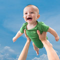 In the sky image of a cheerful little baby father�s hands Stock Image