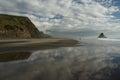 Sky reflecting on karekare beach new zealand Royalty Free Stock Photo