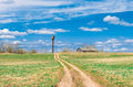 Sky road in the field leading to the shed barn and water tower of the rural landscape of the village. Royalty Free Stock Photo