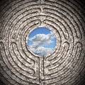 The sky seen through a labyrinth carved in stone business concept toned image Royalty Free Stock Photo