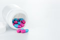 Skyblue and pink pills an pill bottle on white background isolated Royalty Free Stock Image