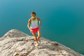 Skyrunner girl runs on a stony back over a lake Royalty Free Stock Photo