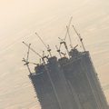 Skyscraper construction site with cranes on top of buildings. Royalty Free Stock Photo